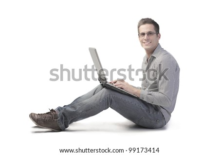 Smiling seated young man using a laptop - stock photo