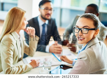 Smiling secretary in eyeglasses looking at camera in working environment