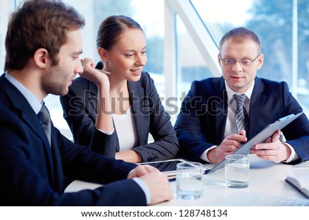 Smiling secretary looking at document held by her boss while listening to his explanation