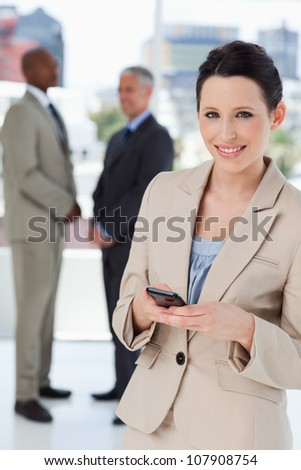 Smiling secretary standing in front of executives while sending a text - stock photo