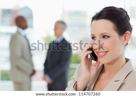 Smiling secretary talking on the phone while looking towards the side - stock photo