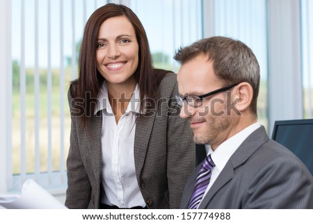 Smiling secretary with her boss standing alongside him as he sits at his desk checking a document she has brought him - stock photo