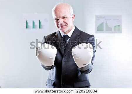 smiling self confident businessman challenging the observer with a pair of boxing gloves