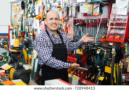 Smiling seller posing near electric compressor in household store