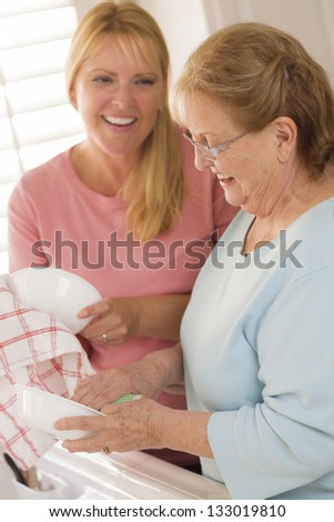 Smiling Senior Adult Woman and Young Daughter Talking At Sink in Kitchen. - stock photo