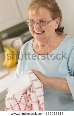 Smiling Senior Adult Woman Drying Bowl At Sink in Kitchen.