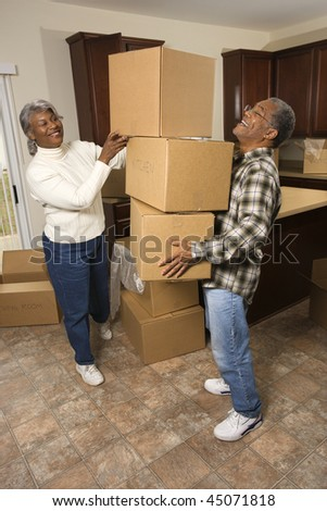 Smiling senior african american man balancing moving boxes while his wife helps. Vertical shot. - stock photo