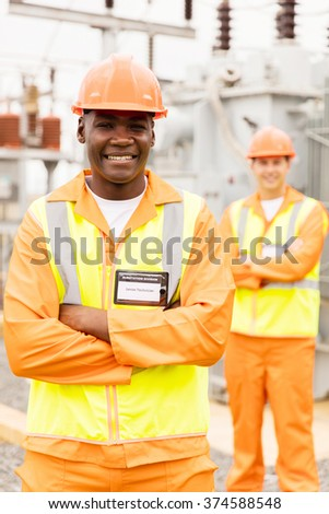 smiling senior african technician with colleague on background in substation - stock photo