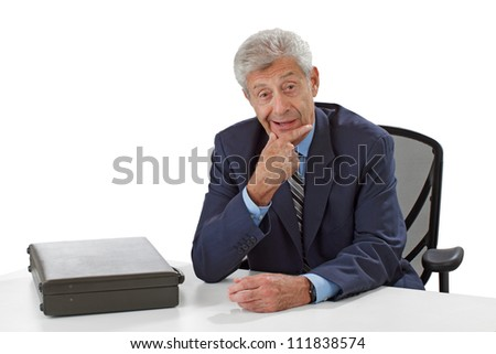 Smiling senior business man in dark suit with closed briefcase sits at desk. He leans forward attentively, hand stroking chin. Horizontal, isolated on white, copy space.