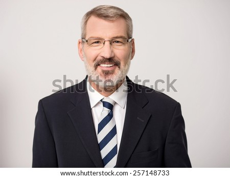 Smiling senior businessman posing to camera