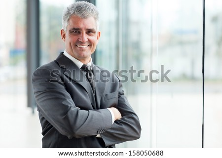 smiling senior businessman with arms crossed - stock photo