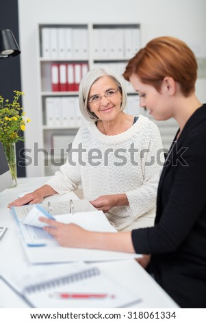 Smiling Senior Businesswoman Assisting her Young Colleague in Reviewing Some Documents.