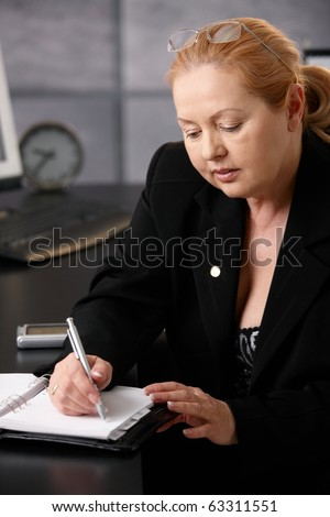 Smiling senior businesswoman taking note, looking at calendar sitting at office desk.?