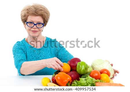 Smiling senior Caucasian woman collects fresh vegetables and fruits on table, isolated on white background - stock photo