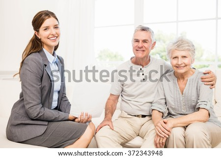 Smiling senior couple and businesswoman holding contract at home - stock photo