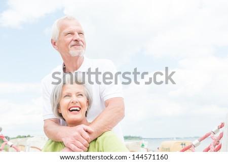 Smiling senior couple at the beach - stock photo