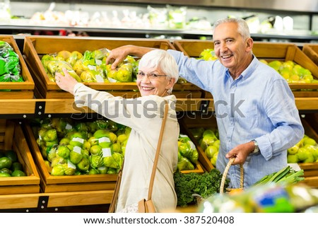 Smiling senior couple at the grocery shop looking at the camera - stock photo