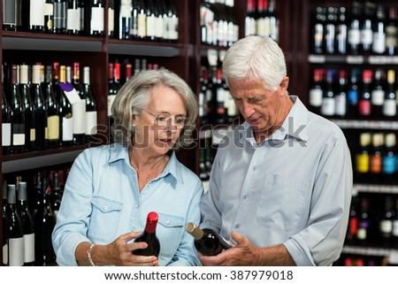 Smiling senior couple choosing wine at the supermarket