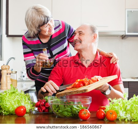 Smiling senior couple cooking  together in home kitchen