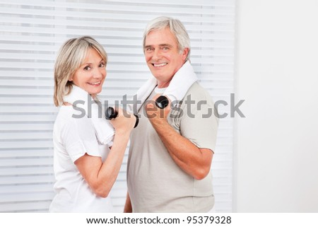 Smiling senior couple doing fitness training with dumbbells in gym