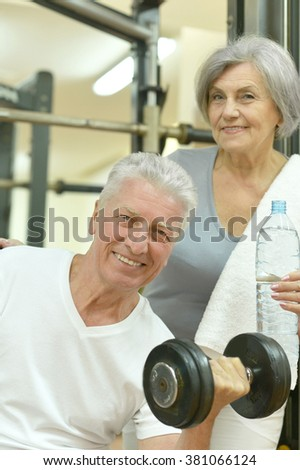 Smiling senior couple drinking water after exercising in gym - stock photo