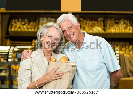 Smiling senior couple holding bakery bag at the bakery store