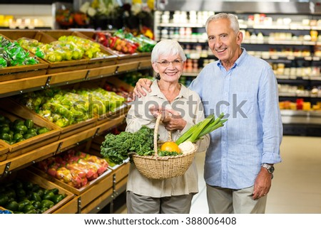 Smiling senior couple holding basket with vegetables at the grocery shop - stock photo