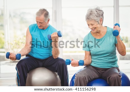 Smiling senior couple holding dumbbells while sitting on exercise ball at home - stock photo