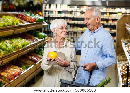 Smiling senior couple holding orange at the grocery shop - stock photo