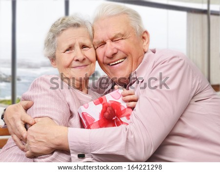 Smiling senior couple hugging at home