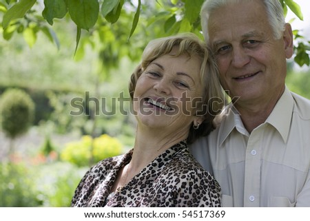 Smiling senior couple in a blossoming garden