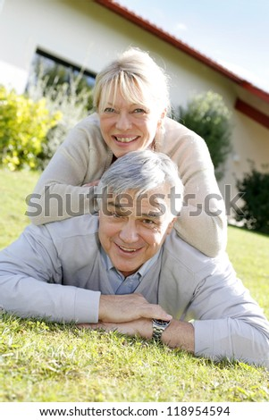 Smiling senior couple laying down the grass - stock photo