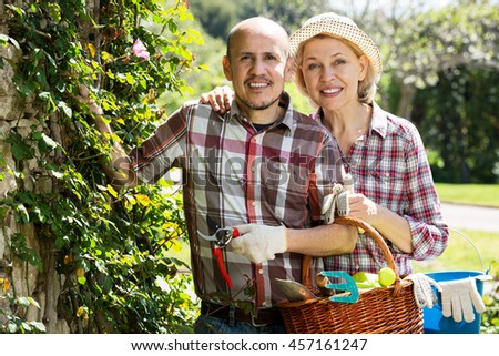 Smiling senior couple looking after flowers in the garden