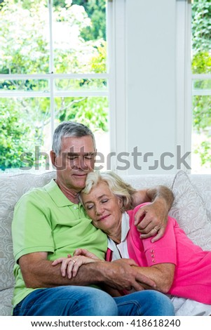 Smiling senior couple relaxing in sitting room at home