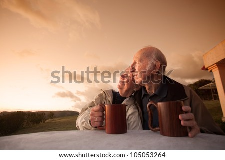 Smiling senior couple sitting outside at sunset - stock photo