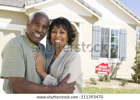 Smiling senior couple standing in front of house for sale - stock photo