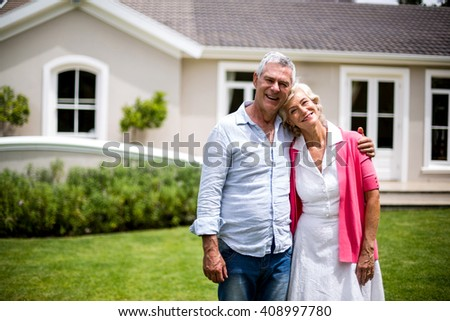 Smiling senior couple with arms around standing outside house in yard - stock photo