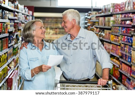 Smiling senior couple with cart and list at the supermarket