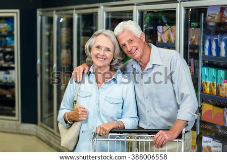 Smiling senior couple with cart looking at the camera in the supermarket