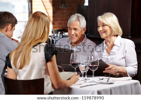 Smiling senior couple with family in a restaurant holding a menu