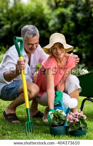 Smiling senior couple with gardening equipment enjoying at yard - stock photo