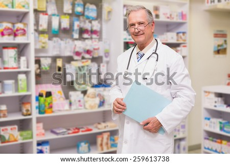 Smiling senior doctor holding files in the pharmacy - stock photo