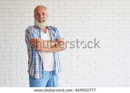 Smiling senior dressed in jeans with checkered shirt standing and crossing his hands, white brick wall in background