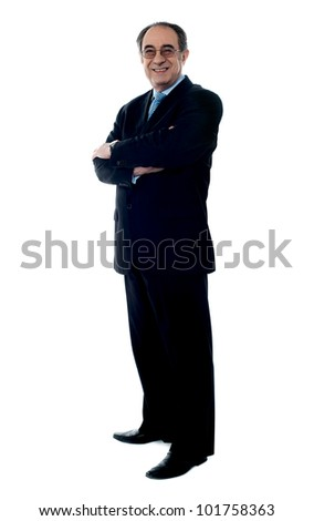 Smiling senior executive posing with folded arms dressed in black suit