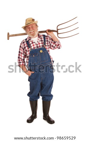 Smiling senior farmer with straw hat, plaid shirt, bib overalls, lifting pitchfork over one shoulder. Vertical layout, isolated on white background with copy space.