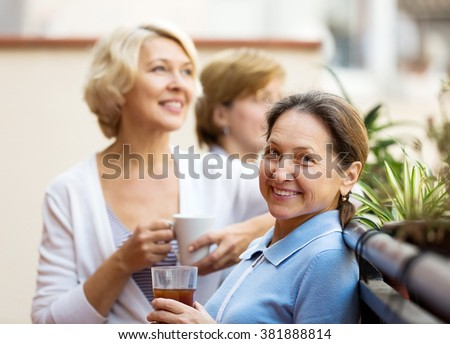 Smiling senior female colleagues having lunch break at patio and drinking tea - stock photo