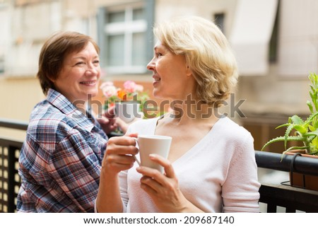 Smiling senior female friends relaxing with cup of coffee on balcony - stock photo