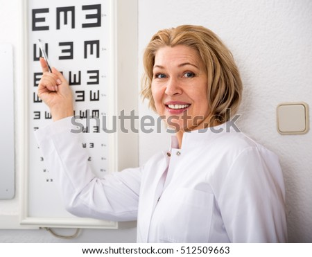 smiling senior female ophthalmologist pointing at letters of eye chart