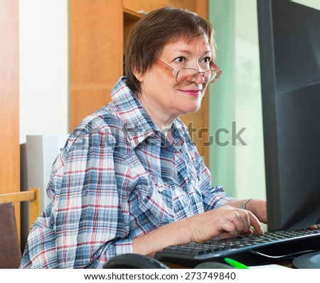 Smiling senior female sitting in front of PC and using keyboard - stock photo