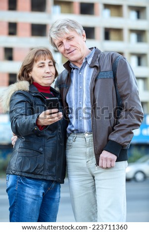 Smiling senior husband and wife looking at cellphone screen together - stock photo
